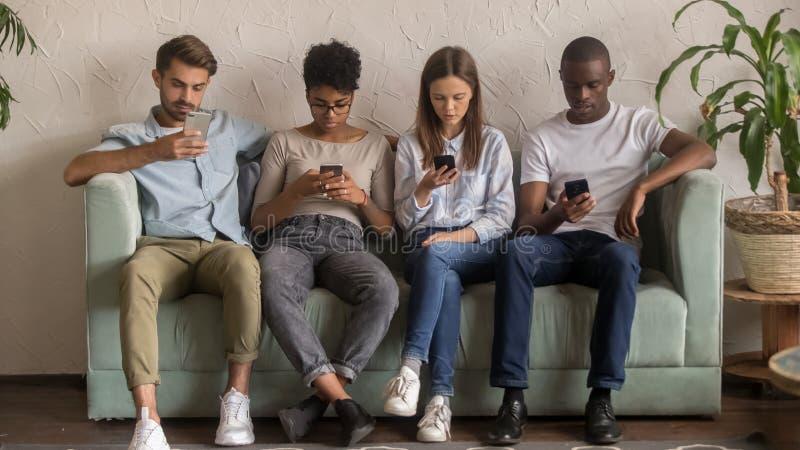 Povos multiculturais que usam os smartphones que ignoram-se que senta-se no sofá fotos de stock royalty free