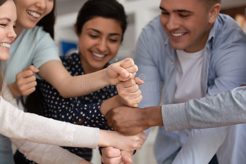 Povos multirraciais excitados contratados na atividade teambuilding na reunião foto de stock