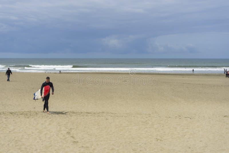 Povos não identificados que andam nos poços do fogo da praia do oceano em San Francisco, CA fotografia de stock