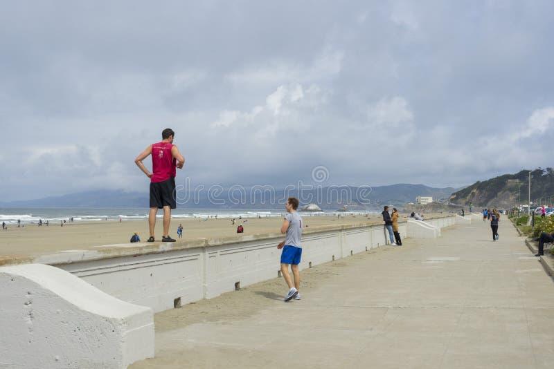 Povos não identificados que andam nos poços do fogo da praia do oceano em San Francisco, CA imagens de stock
