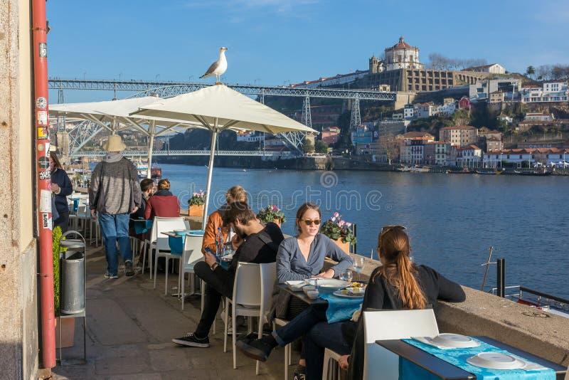 Povos não identificados que têm o almoço no café exterior nos bancos do rio Douro com uma vista bonita na ponte dos DOM Luis de P imagens de stock royalty free