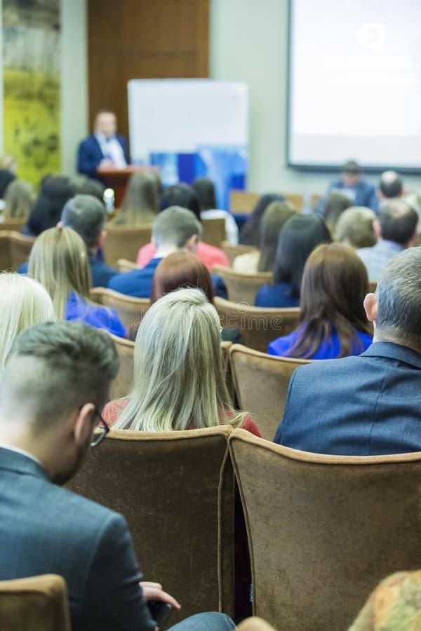Povos na conferência de negócio que escutam o anfitrião chave imagem de stock royalty free
