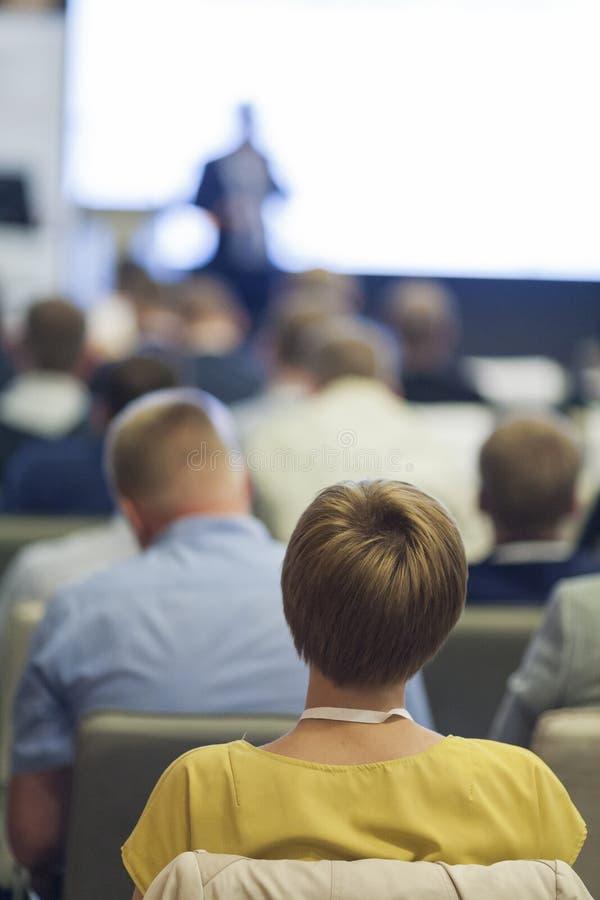 Povos na conferência de negócio que escutam o orador que está na frente de uma placa grande na fase foto de stock royalty free