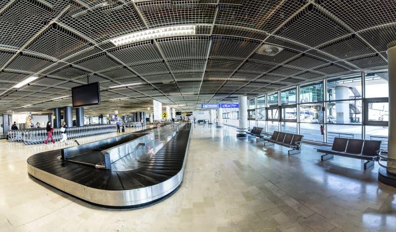 Povos na correia da bagagem dentro do terminal novo no aeroporto de março fotografia de stock royalty free