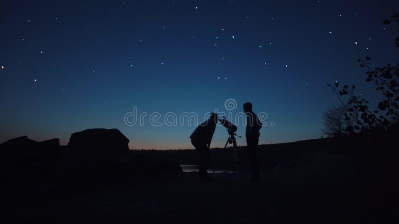 Povos na costa que olha através do telescópio fotografia de stock