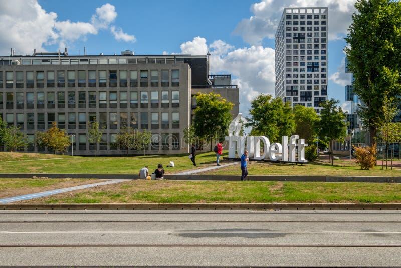 Povos na frente do logotipo da universidade da louça de Delft, Países Baixos foto de stock