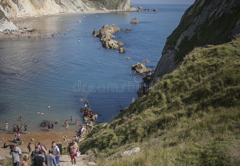 Povos na praia e nas águas azuis da porta de Durdle foto de stock royalty free