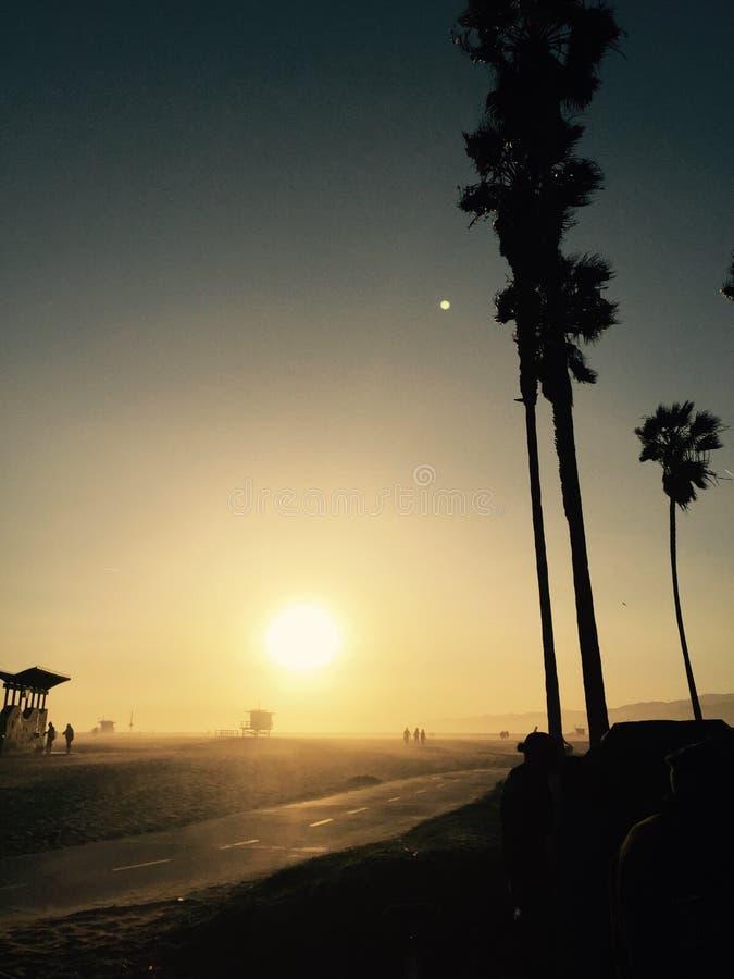 Povos na praia no por do sol em Califórnia do sul imagem de stock