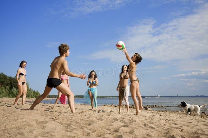 Povos na praia que joga o voleibol fotografia de stock royalty free