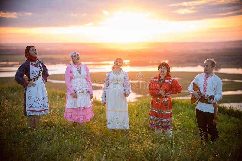 Povos na roupa tradicional do russo que está no campo em um fundo no por do sol brilhante - cante a música fotos de stock