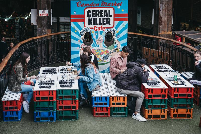 Povos nas tabelas exteriores do café do assassino do cereal em Camden, Londres, Reino Unido fotografia de stock royalty free