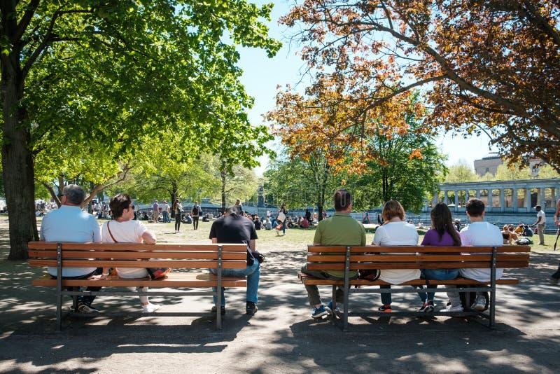 Povos no banco atrás dentro do parque em um ensolarado, dia de verão em Berlim, Alemanha imagem de stock