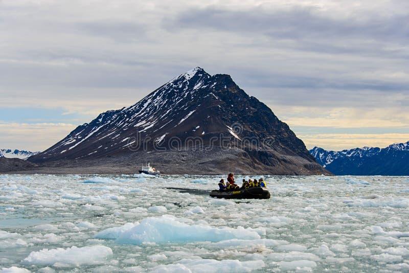 Povos no barco inflável no mar ártico com gelo em Svalbard foto de stock royalty free