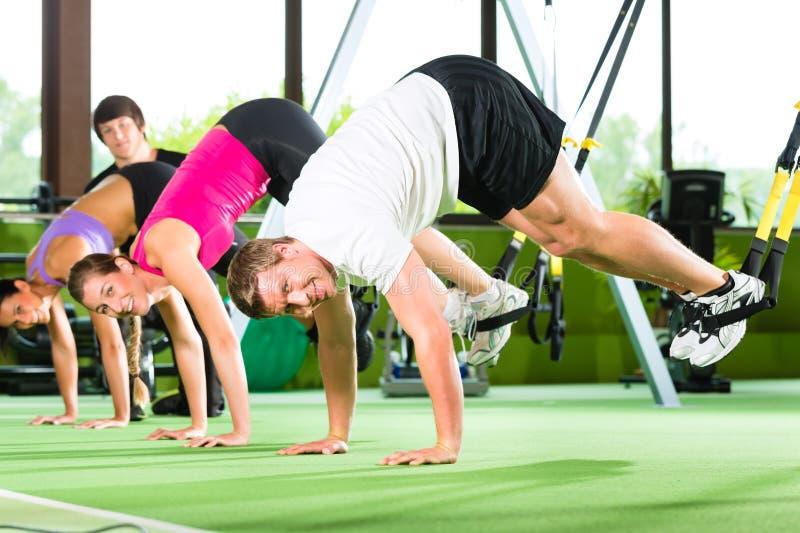 Povos no gym do esporte no instrutor da suspensão imagem de stock royalty free