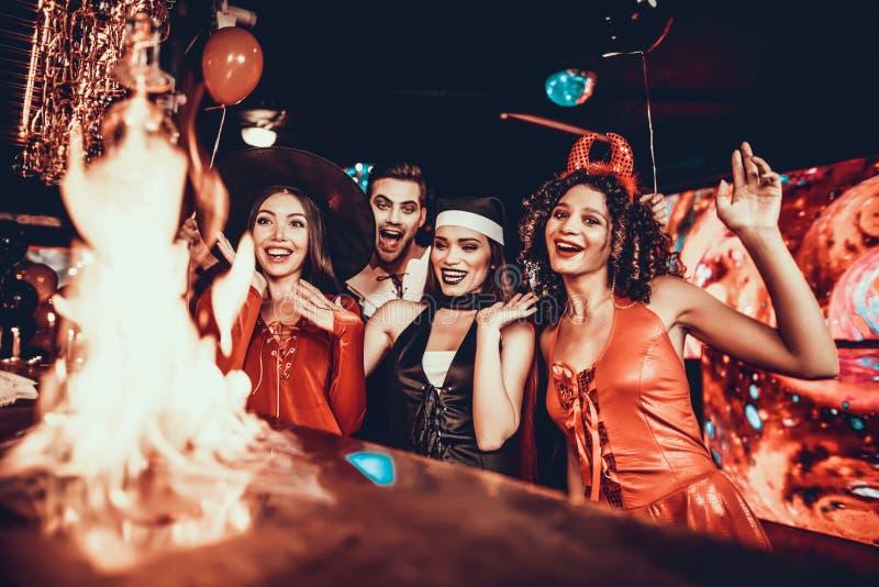 Povos nos trajes que olham cocktail flamejante fotos de stock royalty free