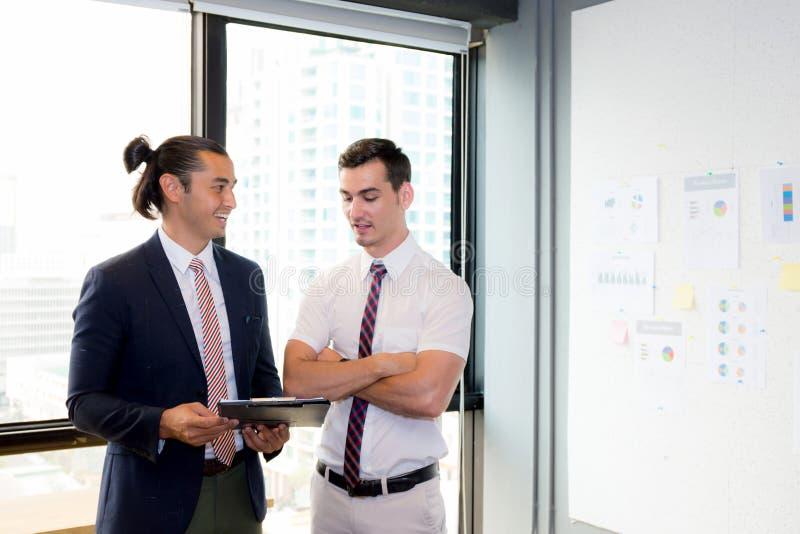Povos novos asiáticos do homem de negócios dois que guardam a prancheta e que discutem o trabalho fotografia de stock