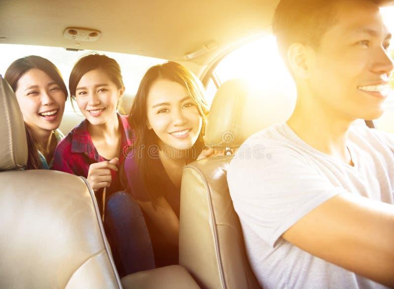 Povos novos do grupo que apreciam a viagem por estrada no carro imagens de stock