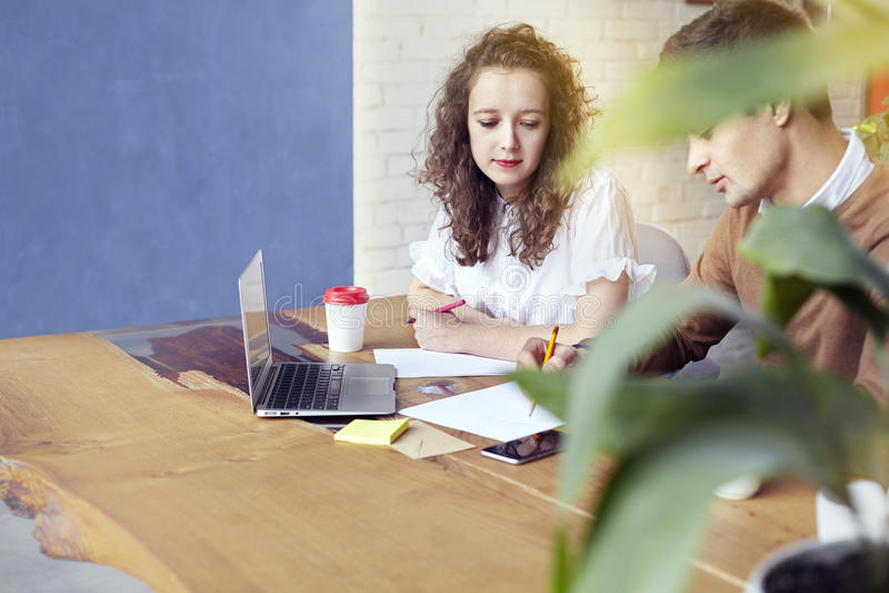 Povos novos dos sócios comerciais que trabalham junto, discutindo a ideia criativa no escritório Encontro Start-up dos colegas de fotos de stock royalty free