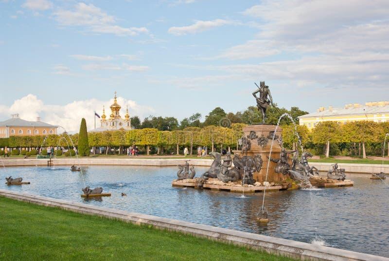 Povos perto da fonte de Netuno na conserva Peterhof do museu do estado Rússia fotos de stock royalty free
