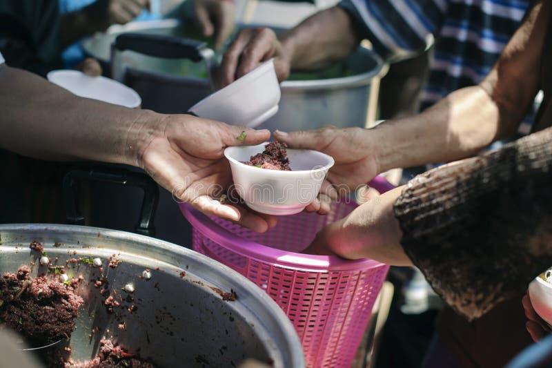 Povos pobres que recebem o alimento das doações: O os sem-abrigo é ajudado com relevo de alimento, relevo da fome: voluntários qu foto de stock