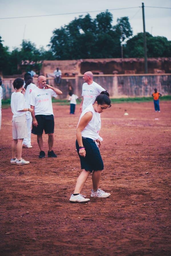 Povos preto e branco que jogam o futebol em uma vila africana rural imagens de stock royalty free