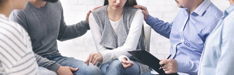 Povos que aconselham a mulher desesperada na sessão de terapia do grupo imagem de stock royalty free