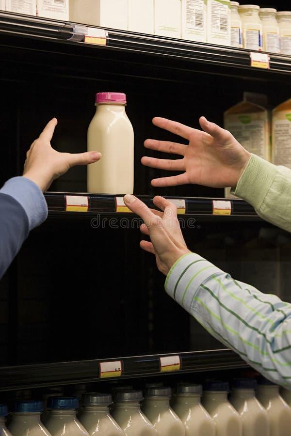 Povos que alcançam para o leite imagens de stock