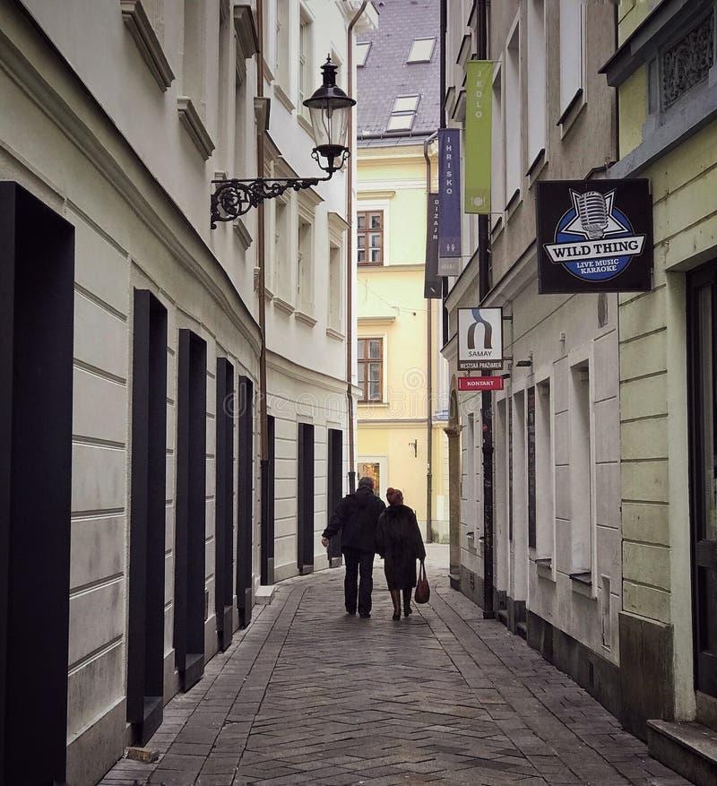 Povos que andam abaixo de uma rua estreita em Bratislava, Eslováquia imagens de stock