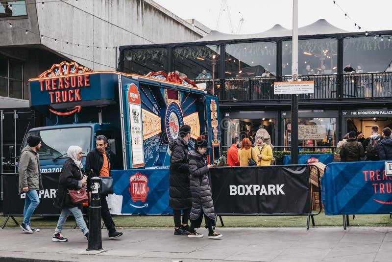 Povos que andam após o caminhão das Amazonas estacionado em BOXPARK Shoreditch, Londres, Reino Unido imagens de stock royalty free