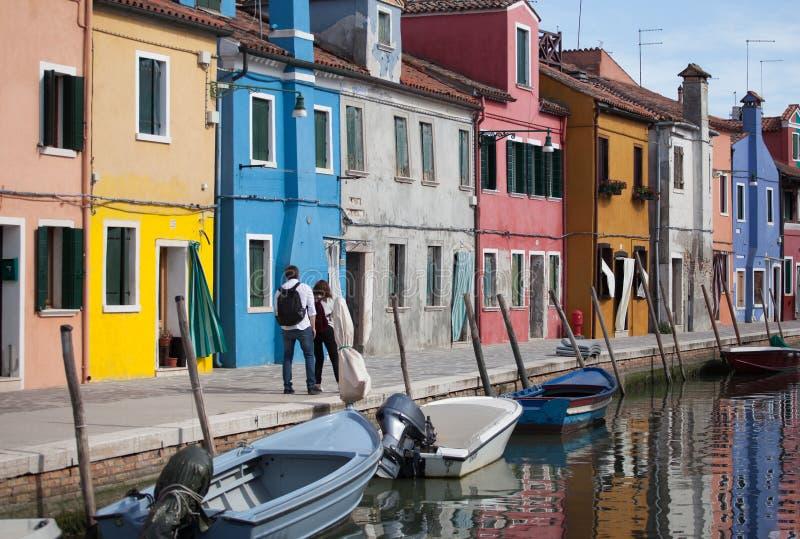 2 povos que andam - casas de Burano e de reflexão na água Vias navegáveis com barcos tradicionais e a fachada colorida Veneza - e imagem de stock