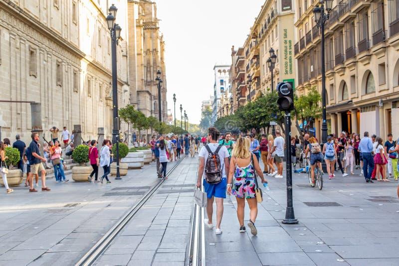 Povos que andam durante o dia em uma rua pedestre perto da catedral em Sevilha, Espanha Marco famoso fotos de stock royalty free