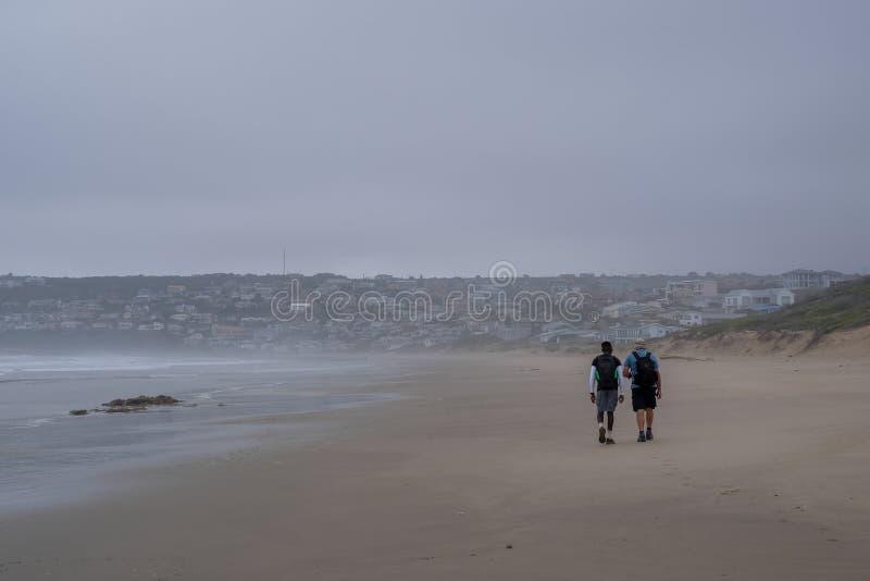 Povos que andam na distância no Sandy Beach na fuga da pega-do-mar, perto da baía de Mossel, rota do jardim, África do Sul imagem de stock royalty free