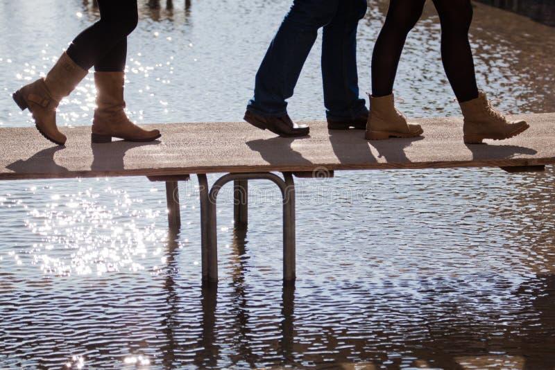 Povos que andam na inundação em um passadiço fotografia de stock
