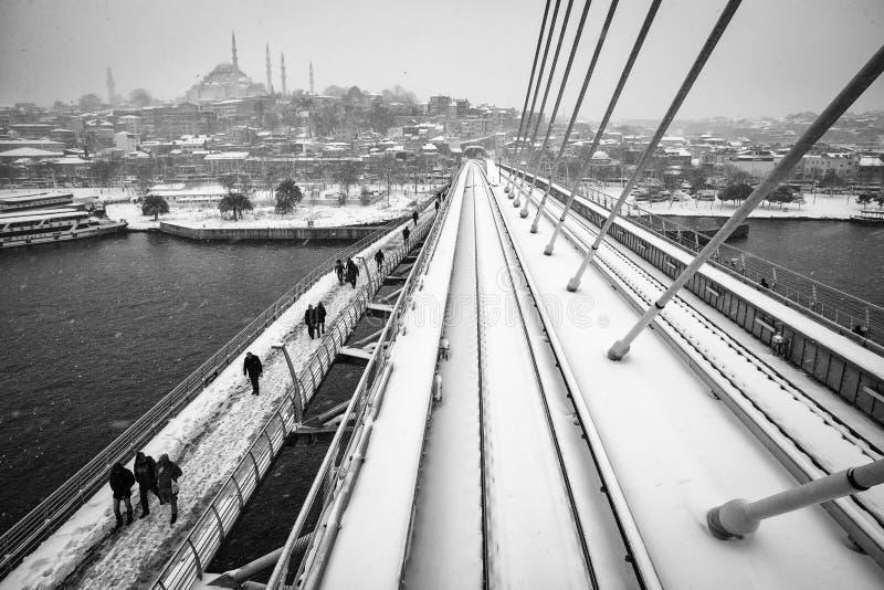 Povos que andam na ponte dourada do metro do chifre em um dia nevado fotografia de stock