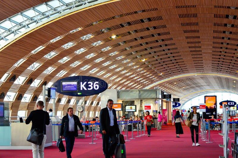 Povos que andam na sala de estar de espera do aeroporto de Paris Charles de Gaulle CDG imagens de stock royalty free