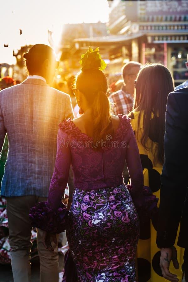 Povos que andam no por do sol ` S April Fair de Sevilha Conceito espanhol do turista imagem de stock