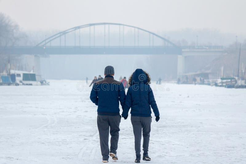 Povos que andam no Tamis congelado do rio em Pancevo, Sérvia devido a um tempo excepcionalmente frio sobre os Balcãs fotografia de stock