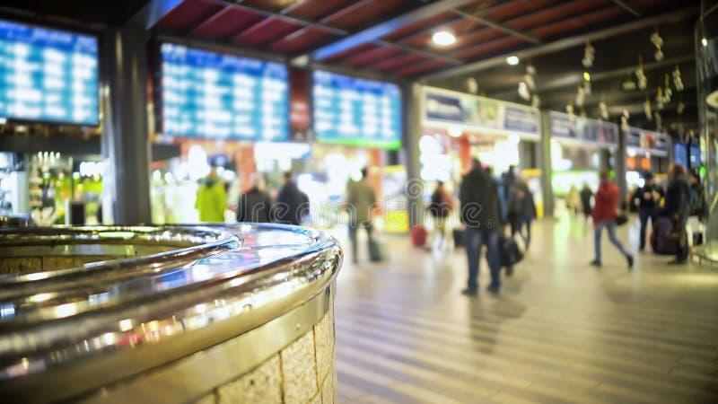 Povos que andam no terminal de aeroporto, nas telas do calendário das chegadas e nas partidas imagem de stock