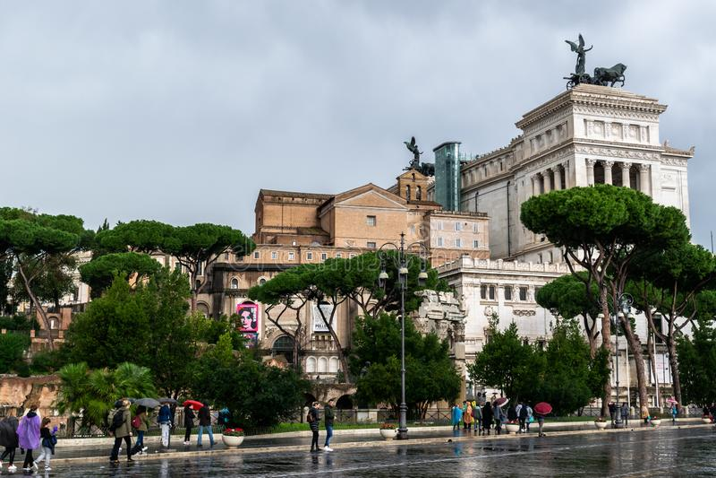 Povos que andam sobre através da rua de Dei Fori Imperiali O monumento de Vittorio Emanuele II altera-se da pátria no fundo foto de stock