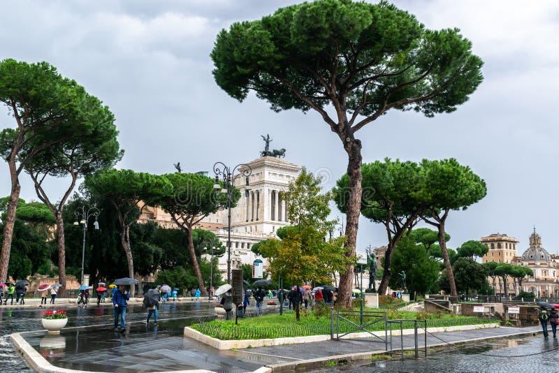 Povos que andam sobre atrav?s da rua de Dei Fori Imperiali O monumento de Vittorio Emanuele II altera-se da p?tria no fundo fotos de stock