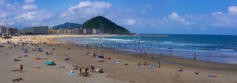Povos que apreciam o sol na praia de Zurriola, cidade de San Sebastian, país Basque imagem de stock
