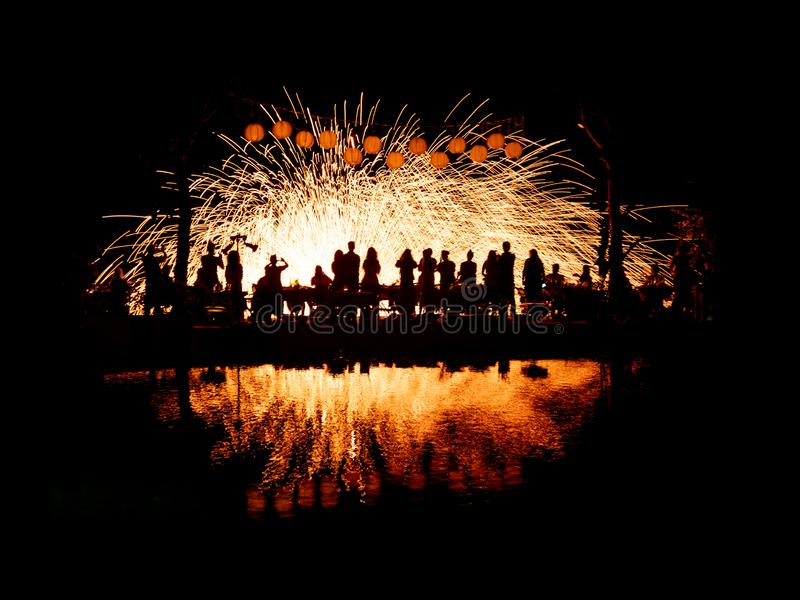 Povos que apreciam uma exposição emocionante do fogo de artifício ao lado de uma associação fotografia de stock