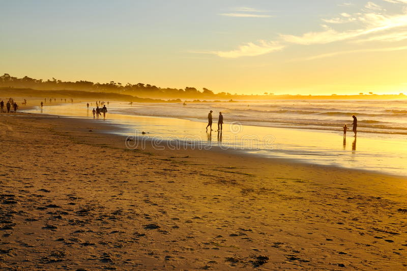 Povos que apreciam uma praia dourada no por do sol imagem de stock