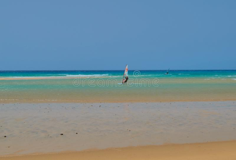 Povos que aprendem surfar em uma praia com ondas e na água de turquesa em Fuerteventura fotografia de stock