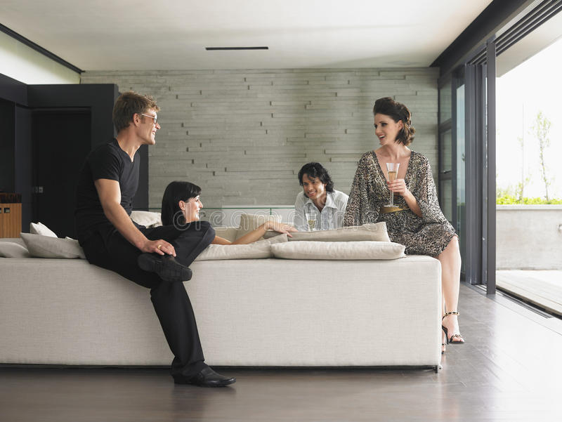Povos que bebem Champagne In Living Room imagens de stock royalty free