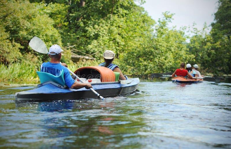Povos que canoeing em um rio pequeno no ver?o imagem de stock