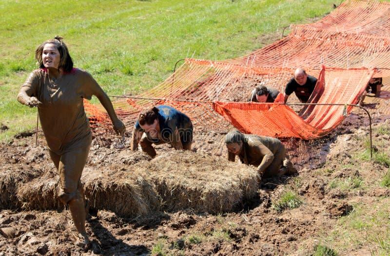 Povos que correm através da lama ao competir em uma corrida da lama foto de stock