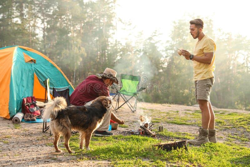 Povos que cozinham na barraca de acampamento próxima da fogueira imagens de stock