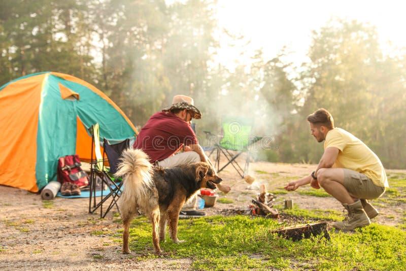 Povos que cozinham na barraca de acampamento próxima da fogueira foto de stock