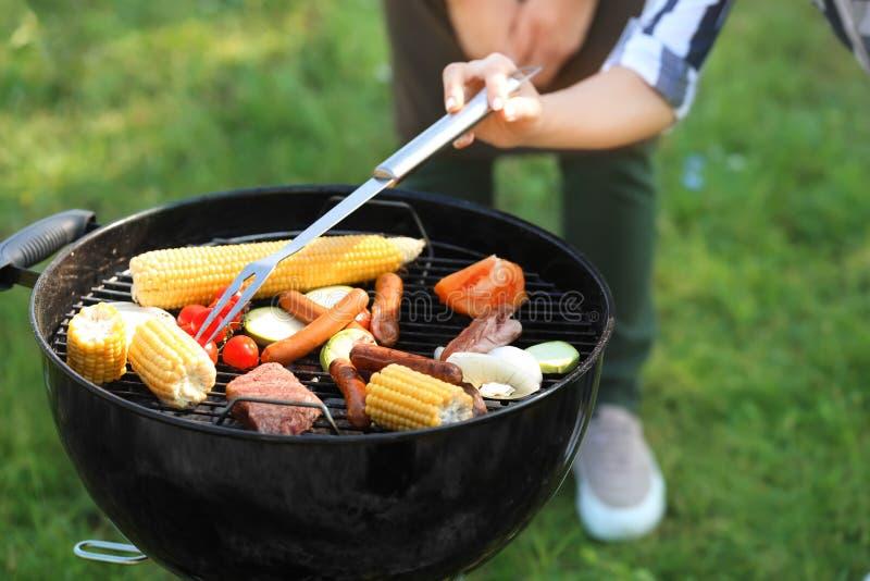 Povos que cozinham o alimento saboroso no ar livre da grade do assado, close up imagens de stock